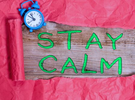 Writing note showing Stay Calm. Business concept for Maintain in a state of motion smoothly even under pressure Alarm clock and torn cardboard on a wooden classic table backdrop