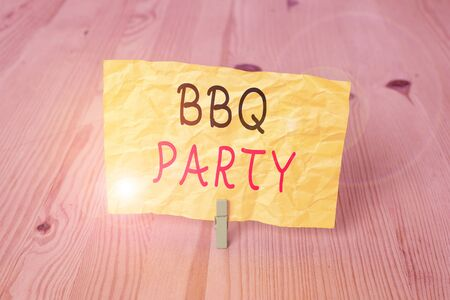 Conceptual hand writing showing Bbq Party. Concept meaning usually done outdoors by smoking meat over wood or charcoal Wooden floor background green clothespin groove slot office