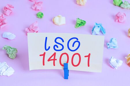 Word writing text Iso 14001. Business photo showcasing a family of standards related to environmental analysisagement Colored crumpled papers empty reminder pink floor background clothespin