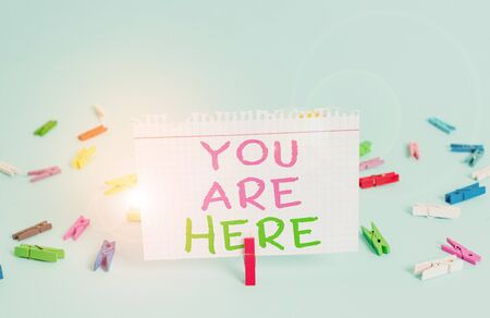 Word writing text You Are Here. Business photo showcasing This is your location reference point global positioning system Colored clothespin rectangle square shaped paper light blue background
