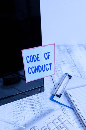 Handwriting text Code Of Conduct. Conceptual photo Ethics rules moral codes ethical principles values respect Note paper taped to black computer screen near keyboard and stationary