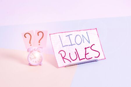 Handwriting text Lion Rules. Conceptual photo epitome of strength power and masculinity Master of own domain Mini size alarm clock beside a Paper sheet placed tilted on pastel backdrop Imagens