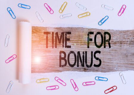 Conceptual hand writing showing Time For Bonus. Concept meaning a sum of money added to a demonstrating s is wages as a reward Paper clip and torn cardboard on wood classic table backdrop