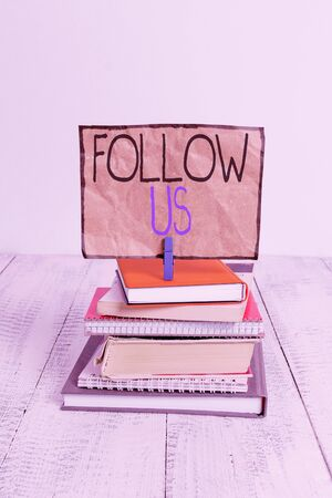 Conceptual hand writing showing Follow Us. Concept meaning To invite a demonstrating or group to join his company and take rules pile stacked books notebook pin color reminder white wooden Stock Photo