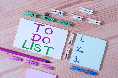 Text sign showing To Do List. Business photo showcasing A structure that usualy made in paper contining task of yours Colored clothespin papers empty reminder wooden floor background office