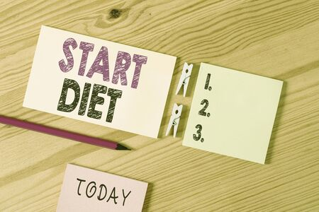 Conceptual hand writing showing Start Diet. Concept meaning special course food to which demonstrating restricts themselves Colored crumpled papers wooden floor background clothespin