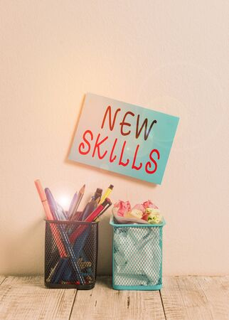 Text sign showing New Skills. Business photo text Recently Acquired Learned Abilities Knowledge Competences Blue Sticky Card on Wall Two Pencil Pots Pens Pencils Markers Waste Paper