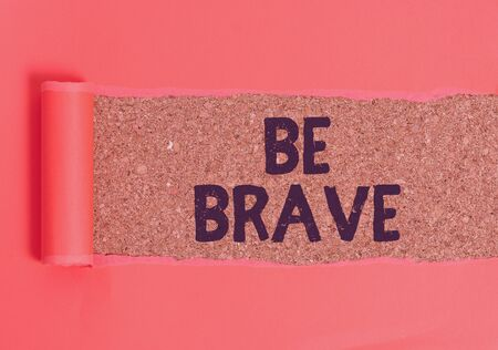 Text sign showing Be Brave. Business photo text ready to face and endure danger or pain showing courage Bold Cardboard which is torn in the middle placed above a wooden classic table