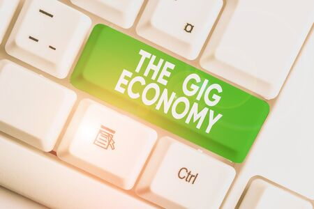 Writing note showing The Gig Economy. Business concept for Market of Shortterm contracts freelance work temporary White pc keyboard with note paper above the white background