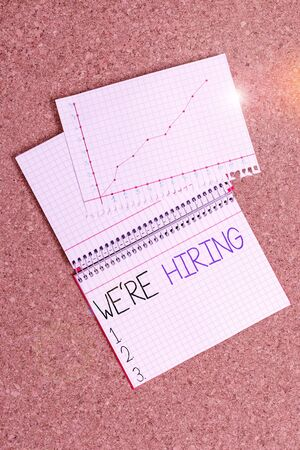Text sign showing We Re Hiring. Business photo showcasing recently you employ someone or pay someone to do particular job Desk notebook paper office cardboard paperboard study supplies table chart Archivio Fotografico