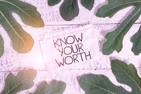 Writing note showing Know Your Worth. Business concept for Have knowledge of selfvalue Worthiness Deserved income Leaves surrounding notepaper above a classic wooden table