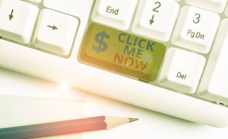 Handwriting text Click Me Now. Conceptual photo Internet helping desk Press the button Online Icon Nertwork White pc keyboard with empty note paper above white background key copy space Imagens