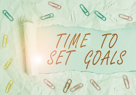 Text sign showing Time To Set Goals. Business photo text Desired Objective Wanted to accomplish in the future Paper clip and torn cardboard placed above a plain pastel table backdrop