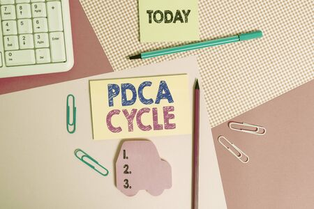 Writing note showing Pdca Cycle. Business concept for use to control and continue improve the processes and products Writing equipments and computer stuffs placed above colored plain table
