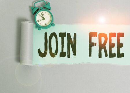 Text sign showing Join Free. Business photo showcasing the act or an instance of joining a group or organization Alarm clock and torn cardboard placed above plain pastel table backdrop