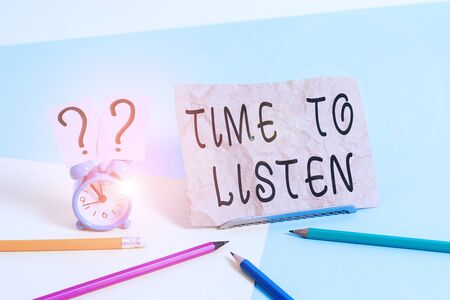 Conceptual hand writing showing Time To Listen. Concept meaning Give attention to someone or something in order to hear Mini size alarm clock beside stationary on pastel backdrop