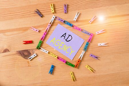 Word writing text Ad Agency. Business photo showcasing business dedicated to creating planning and handling advertising Colored clothespin papers empty reminder wooden floor background office