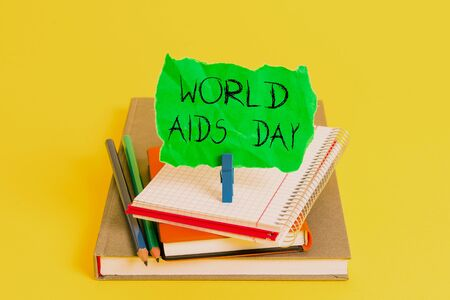 Text sign showing World Aids Day. Business photo showcasing 1st December dedicated to raising awareness of the AIDS Book pencil rectangle shaped reminder notebook clothespin office supplies Archivio Fotografico