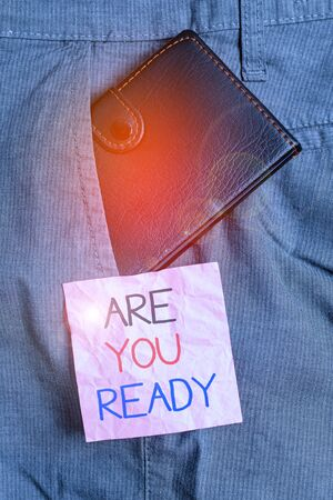 Text sign showing Are You Ready. Business photo text Alertness Preparedness Urgency Game Start Hurry Wide awake Small little wallet inside man trousers front pocket near notation paper