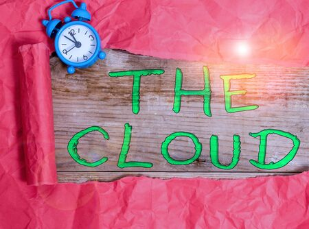 Writing note showing The Cloud. Business concept for Programs used in Storing Accessing data over the internet Alarm clock and torn cardboard on a wooden classic table backdrop