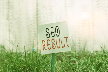 Text sign showing Seo Result. Business photo showcasing the list created by search engines in response to a query Plain empty paper attached to a stick and placed in the green grassy land