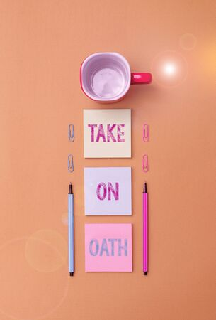 Text sign showing Take On Oath. Business photo text A solemn appeal to a deity Speak the truth Make a Promise Coffee cup blank colored sticky note two ballpoints clips yolk background