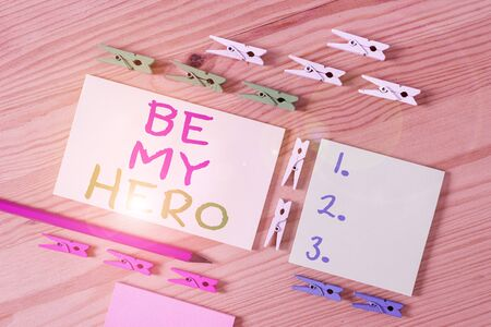 Text sign showing Be My Hero. Business photo showcasing Request by someone to get some efforts of heroic actions for him Colored clothespin papers empty reminder wooden floor background office