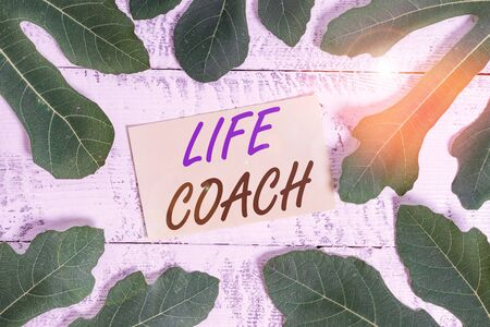 Writing note showing Life Coach. Business concept for someone who helps identify your goals and plan to achieve them Leaves surrounding notepaper above a classic wooden table