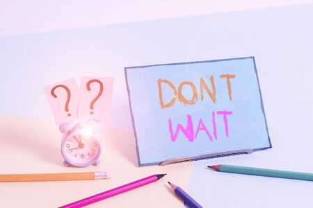 Writing note showing Don T Wait. Business concept for Take action now and do something for a purpose Act quickly Mini size alarm clock beside stationary on pastel backdrop Stock Photo - 134301942