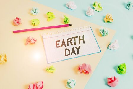 Word writing text Earth Day. Business photo showcasing Worldwide celebration of ecology environment preservation Colored crumpled papers empty reminder blue yellow background clothespin