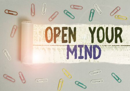 Handwriting text Open Your Mind. Conceptual photo Be openminded Accept new different things ideas situations Paper clip and torn cardboard placed above a wooden classic table backdrop