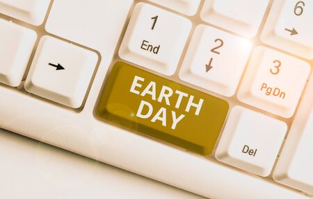 Writing note showing Earth Day. Business concept for Worldwide celebration of ecology environment preservation White pc keyboard with note paper above the white background