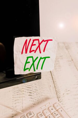 Handwriting text Next Exit. Conceptual photo the following way out or act of leaving in a place or highway Notation paper taped to black computer monitor screen near white keyboard