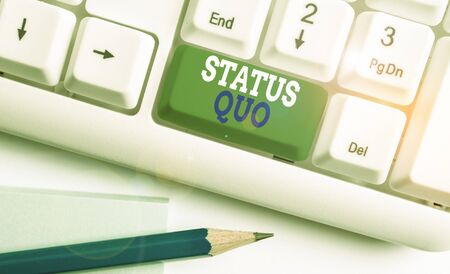 Text sign showing Status Quo. Business photo text existing state of affairs regarding social or political issues White pc keyboard with empty note paper above white background key copy space