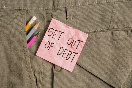 Text sign showing Get Out Of Debt. Business photo text No prospect of being paid any more and free from debt Writing equipment and pink note paper inside pocket of man work trousers Foto de archivo