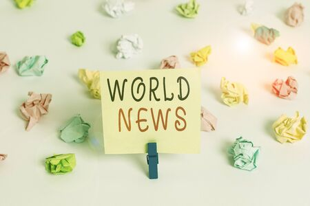 Word writing text World News. Business photo showcasing global noteworthy information about recent or important events Colored crumpled papers empty reminder white floor background clothespin
