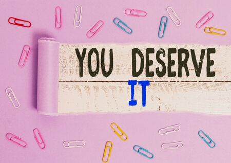 Handwriting text You Deserve It. Conceptual photo Reward for something well done Deserve Recognition award Paper clip and torn cardboard placed above a wooden classic table backdrop