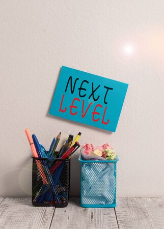 Text sign showing Next Level. Business photo text having more than one floor and referring to after current Blue Sticky Card on Wall Two Pencil Pots Pens Pencils Markers Waste Paper