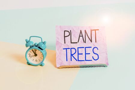 Handwriting text writing Plant Trees. Conceptual photo process of planting a tree for land cultivation and forestry Mini size alarm clock beside a Paper sheet placed tilted on pastel backdrop