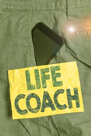 Writing note showing Life Coach. Business concept for someone who helps identify your goals and plan to achieve them Smartphone device inside trousers front pocket note paper