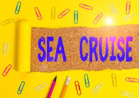 Conceptual hand writing showing Sea Cruise. Concept meaning a voyage on a ship or boat taken for pleasure or as a vacation Stationary and torn cardboard on a wooden classic table backdrop