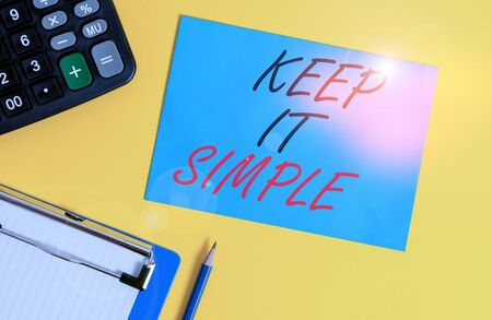 Writing note showing Keep It Simple. Business concept for Easy to toss around Understandable Generic terminology Clipboard blank sheet square page calculator pencil colored background