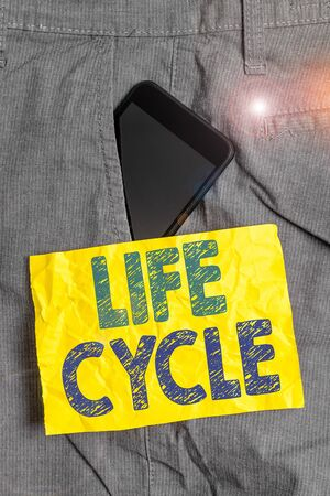 Writing note showing Life Cycle. Business concept for the series of changes in the life of an organism and animals Smartphone device inside trousers front pocket note paper Zdjęcie Seryjne - 134312831