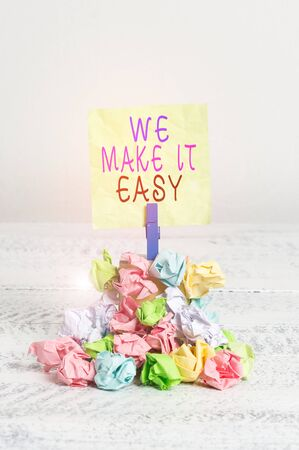 Writing note showing We Make It Easy. Business concept for Offering solutions alternatives make an easier job ideas Reminder pile colored crumpled paper clothespin wooden space