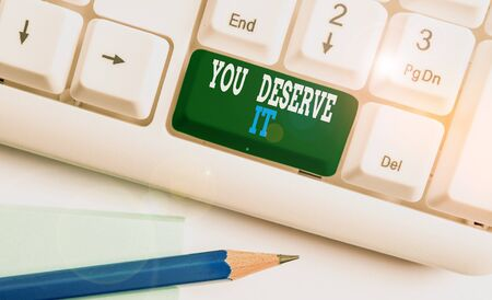 Text sign showing You Deserve It. Business photo showcasing Reward for something well done Deserve Recognition award White pc keyboard with empty note paper above white background key copy space