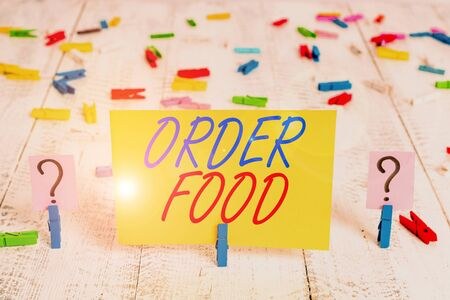 Writing note showing Order Food. Business concept for the process of requesting a preferred food in a restaurant Crumbling sheet with paper clips placed on the wooden table Stock Photo