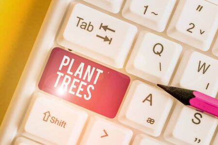 Word writing text Plant Trees. Business photo showcasing process of planting a tree for land cultivation and forestry White pc keyboard with empty note paper above white background key copy space Zdjęcie Seryjne - 134313431