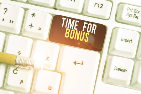 Text sign showing Time For Bonus. Business photo text a sum of money added to a demonstrating s is wages as a reward White pc keyboard with empty note paper above white background key copy space