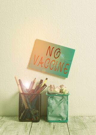 Text sign showing No Vaccine. Business photo text not provided of immunity against one or several diseases Blue Sticky Card on Wall Two Pencil Pots Pens Pencils Markers Waste Paper