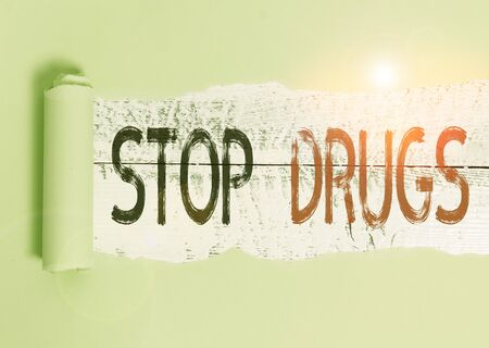 Conceptual hand writing showing Stop Drugs. Concept meaning put an end on dependence on substances such as heroin or cocaine Cardboard which is torn placed above a wooden classic table